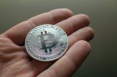 Mano del hombre de negocios que lleva a cabo la muestra del bitcoin que brilla intensamente en fondo interior Foto de archivo libre de regalías