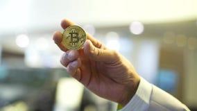 Mano del hombre de negocios que lleva a cabo la muestra del bitcoin que brilla intensamente existencias Concepto virtual del dine almacen de video