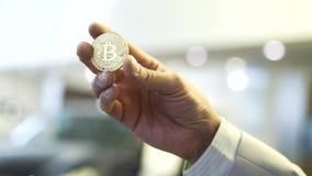 Mano del hombre de negocios que lleva a cabo la muestra del bitcoin que brilla intensamente existencias Concepto virtual del dine metrajes