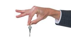 Mano del hombre de negocios que lleva a cabo llave Imagen de archivo libre de regalías