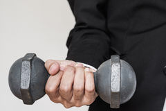 Mano del hombre de negocios que lleva a cabo pesa de gimnasia pesada fotos de archivo
