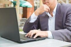 Mano del hombre de negocios que mecanografía en el cuaderno o el ordenador portátil Imagen de archivo