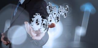 Mano del hombre de negocios que muestra el engranaje 3d al éxito Imagenes de archivo