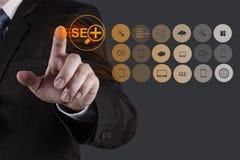 Mano del hombre de negocios que muestra la optimización SEO del Search Engine Foto de archivo libre de regalías