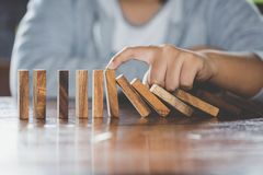 Mano del hombre de negocios que para efecto de dominós de madera descendente de c imagen de archivo libre de regalías