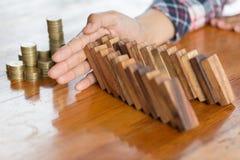 Mano del hombre de negocios que para efecto de dominós de madera descendente de c imagen de archivo