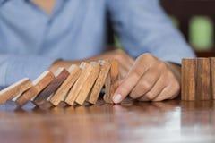 Mano del hombre de negocios que para efecto de dominós de madera descendente de haber derribado continuo o riesgo, estrategia e i imagenes de archivo