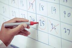 Mano del hombre de negocios que planea su horario en el whiteboard fotos de archivo libres de regalías