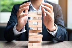 Mano del hombre de negocios que pone o que tira del bloque de madera en la torre Planificación de empresas, gestión de riesgos foto de archivo