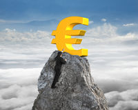 Mano del hombre de negocios que quiere para el símbolo euro en pico con el cloudscape Imagen de archivo
