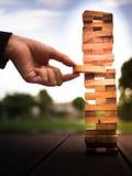 Mano del hombre de negocios que saca o que pone el bloque de madera en la torre Plan y estrategia en negocio falta de definición  Imagen de archivo libre de regalías