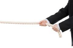 Mano del hombre de negocios que se sostiene o cuerda de tracción Imagen de archivo