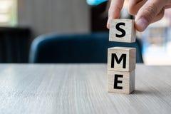 Mano del hombre de negocios que sostiene el cubo de madera con empresa media del texto de la PME pequeña en fondo de la tabla Fin fotografía de archivo libre de regalías