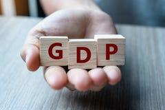 Mano del hombre de negocios que sostiene el cubo de madera con el producto interno bruto del texto del GDP en fondo de la tabla F fotos de archivo