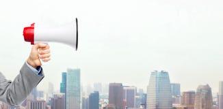Mano del hombre de negocios que sostiene el megáfono Foto de archivo libre de regalías