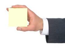 Mano del hombre de negocios que sostiene el post-it amarillo Imagen de archivo libre de regalías