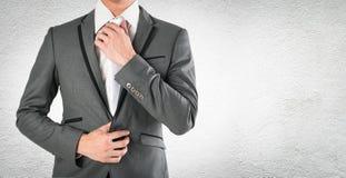 Mano del hombre de negocios que sostiene la corbata en la habitación gris en cbac concreto foto de archivo