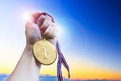 Mano del hombre de negocios que sostiene la medalla de oro de la moneda imagen de archivo libre de regalías