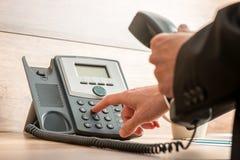 Mano del hombre de negocios que sostiene un receptor de teléfono de la línea horizonte que marca a Fotografía de archivo libre de regalías