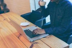 Mano del hombre de negocios usando el ordenador portátil en café del café Fotografía de archivo