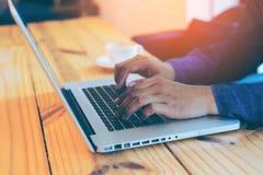 Mano del hombre de negocios usando el ordenador portátil en café del café Fotografía de archivo libre de regalías