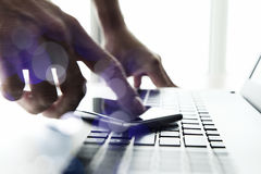 Mano del hombre de negocios usando el ordenador portátil y el teléfono móvil Fotos de archivo libres de regalías