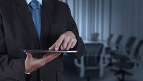Mano del hombre de negocios usando el ordenador y la sala de juntas de la tableta Imagen de archivo