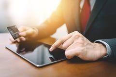 Mano del hombre de negocios usando la tableta y la tarjeta de crédito Fotografía de archivo