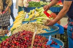 Mano del hombre del vendedor que pone las moras blancas en una taza plástica con la pala roja en un bazar turco típico del ultram foto de archivo libre de regalías