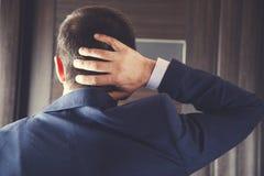 Mano del hombre en cuello foto de archivo