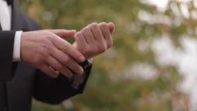 Mano del hombre en traje negro afuera almacen de video