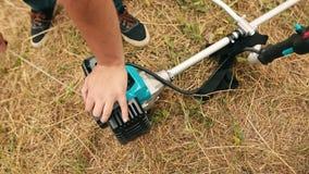 Mano del hombre del jardinero que enciende el condensador de ajuste del césped del gas Manos de un cortacésped profesional metrajes
