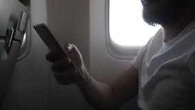Mano del hombre joven que detiene el smartphone en el avión, cierre almacen de metraje de vídeo