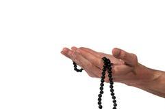 Mano del hombre musulmán que ruega con el rosario imagenes de archivo