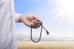 Mano del hombre musulmán que ruega mientras que lleva a cabo el tasbih Imagen de archivo libre de regalías