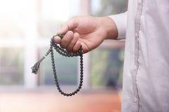 Mano del hombre musulmán que ruega mientras que lleva a cabo el tasbih Imágenes de archivo libres de regalías