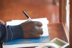 Mano del hombre negro con la pluma Fotografía de archivo libre de regalías