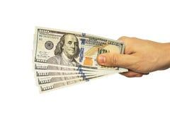 mano del hombre que da 100 billetes de dólar Imagenes de archivo