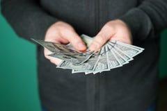 Mano del hombre que da 100 billetes de dólar en estudio Imagen de archivo