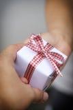 Mano del hombre que da una caja de regalo Fotografía de archivo libre de regalías