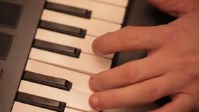 Mano del hombre que juega un sintetizador del teclado del controlador midi metrajes