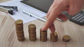 Mano del hombre que lleva a cabo el dólar de la moneda en la pila de la moneda del dinero dispuesta como gráfico en la tabla de m almacen de metraje de vídeo