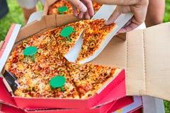 Mano del hombre que lleva a cabo una rebanada de pizza delicous foto de archivo