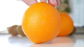 Mano del hombre que presenta una calidad jugosa y buena dulce fruta anaranjada en la tabla metrajes