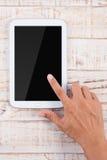 Mano del hombre que señala el teléfono de la tableta en el fondo de madera de la tabla Fotografía de archivo