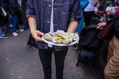 Mano del hombre que sostiene la ostra cruda fresca en placa del paperr con el lim?n en mercado imagen de archivo