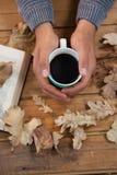 Mano del hombre que sostiene la taza de café sólo y de hojas de otoño en la tabla Fotografía de archivo