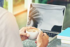Mano del hombre que sostiene las tazas de café del latte con el funcionamiento del ordenador portátil en cof foto de archivo