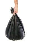 Mano del hombre que sostiene un bolso de basura fotografía de archivo libre de regalías