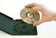 Mano del hombre que sostiene un disco compacto tomado de un rectángulo Imagen de archivo libre de regalías